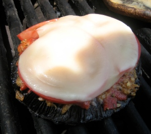 Bruschetta filling, tomato, and provolone melting on portabella
